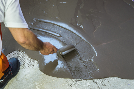 bracket: Worker puts a self leveling screed on cement floor