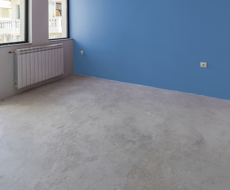 garage: Unfinished interior of apartment  under construction with gray concrete floor, windows and color wall Stock Photo