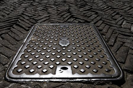 Old shaft cover on the paving street 写真素材