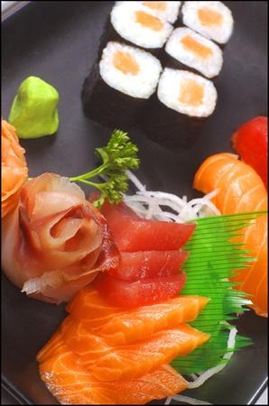 noire: Une assiette noire avec des sashimis thon et saumon en premier plan, deux bouts de sushi thon et saumon, et 6 maki saumon Stock Photo
