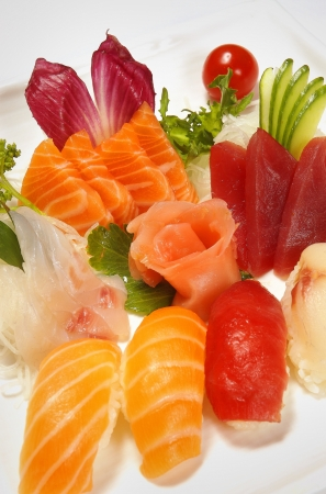 tobikko: Sushi and sashimi on a plate, with a cherry tomato in the background