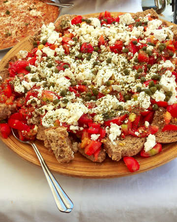 Greek dakos, barley bread, tomatoes, feta cheese, capers, olive oil, oregano photo