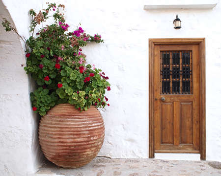 old building facade: house door and huge flower jar, Greece Stock Photo