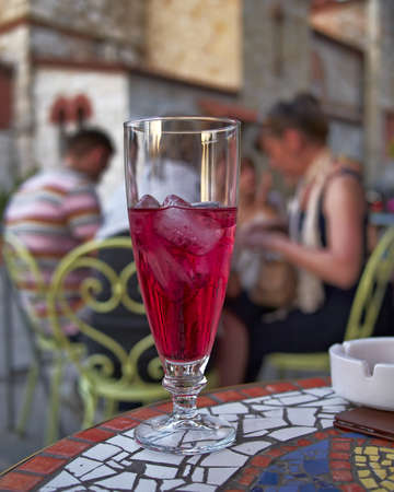 grenadine: ice tea with grenadine syrup and people chatting  out of focus