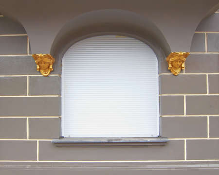 white shutters window decorated with golden faces, Berlin Germany photo