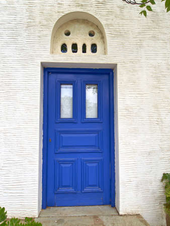 bass relief: blue door with marble bass-relief on white wall, mediterranean island