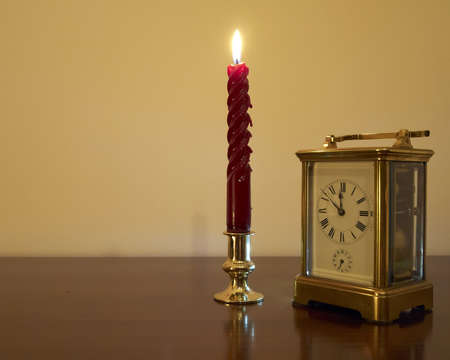 Old bronze clock and candle  minutes before New Year, room for type photo