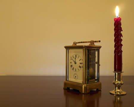 Old bronze clock and candle  minutes before New Year, room for typing photo