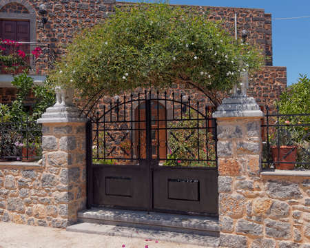 gate: house entrance and jasmin plant arch Stock Photo