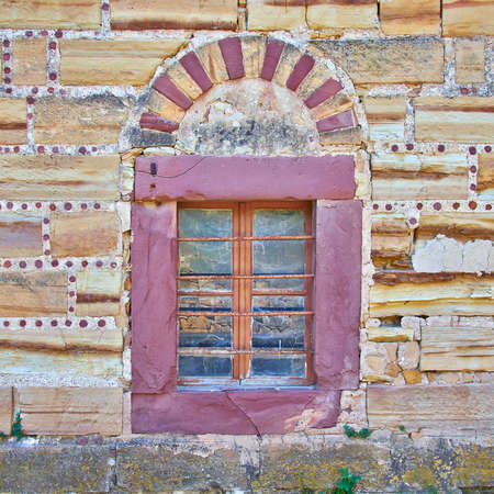 arched window on  red and ocher colored stone wall, vintage building detail Stock Photo
