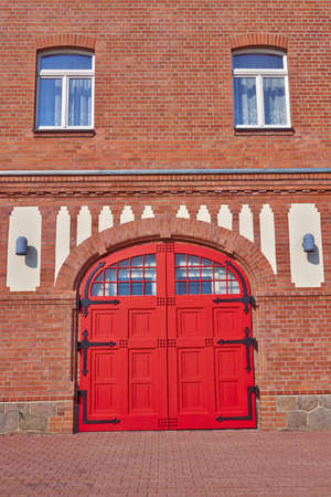 entrance with arched red door and windows, central Europe photo
