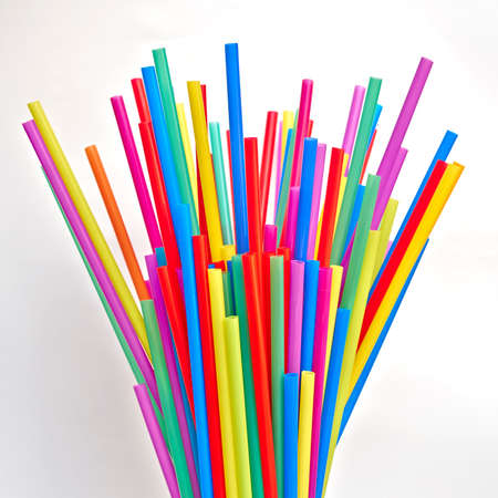 variety of colorful drinking straws on white paper photo