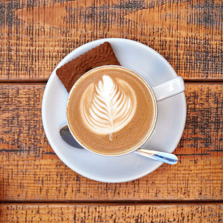 delicious art capuccino cup on wooden background