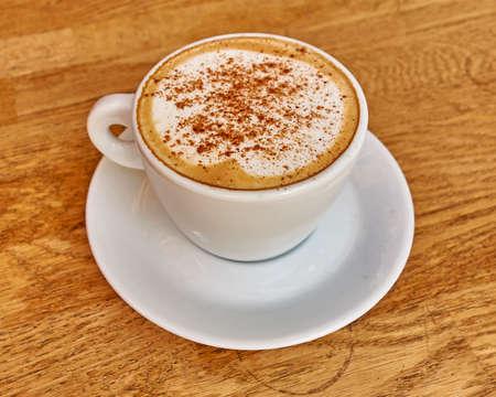 Cappuccino in witte kop close-up op houten achtergrond