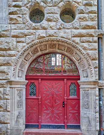 arched: vintage arched red door on stone wall