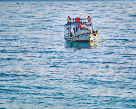 commercial fisheries: Greek traditional Kaiki fishing boat pulling nets out of the sea