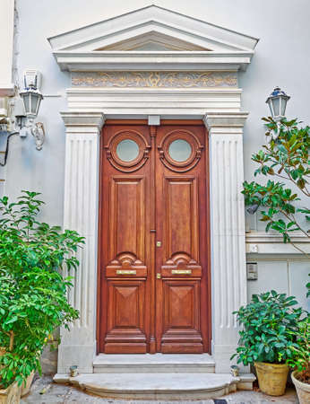 pediment: vintage house entrance with pediment and solid wood door, Athens Greece Stock Photo