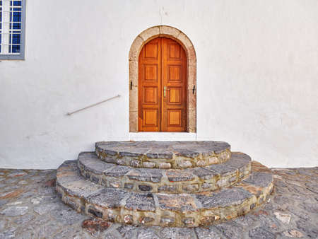 Greece, vintage wooden arched door and round stairs entrance Stock Photo