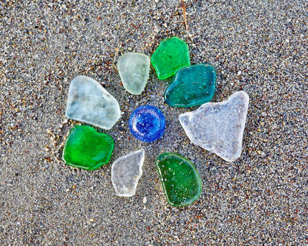 pices: colorful glass pices polished by the sea on wet sand beach