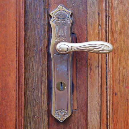 古いヴィンテージ ドア ハンドル、茶色ウッドの背景 写真素材