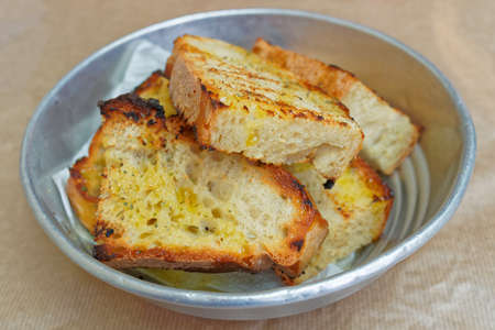 sliced bread roasted with vorgin olive oil and oregano in metalic dish