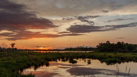 Sunset with clouds reflecting in a pond at Merritt Island National Wildlife Refuge, Florida, USA Stock Photo
