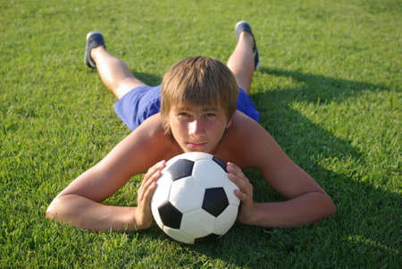pubertad: Un ni�o con un bal�n de f�tbol Foto de archivo