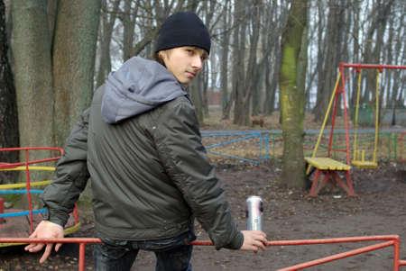 Boy sitting in playground drinking beer Stock Photo