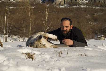 Man with dog in winter forest photo