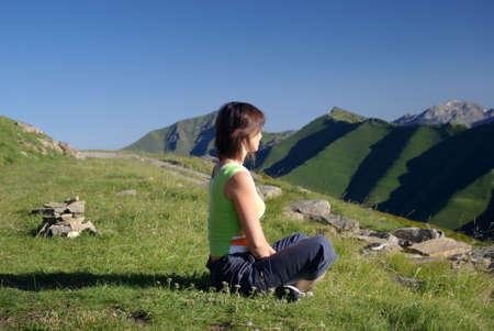 Mujer sentada sobre hierba en montañas relajantes