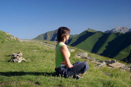 Woman sitting on grass in mountains relaxing Stock Photo