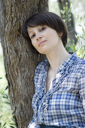 Woman leaning against tree Stock Photo - 9492913