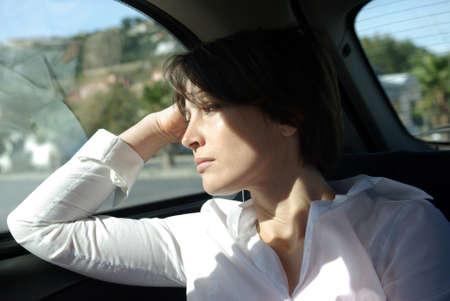 Mujer en el asiento trasero del coche mirando de ventana Foto de archivo