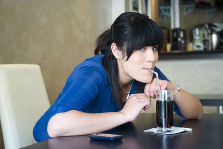 Adolescente en la barra de bebida cola