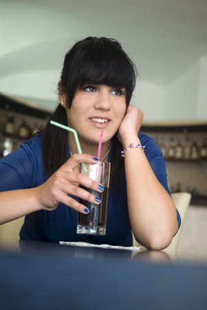 Teenage girl in the bar drinking cola