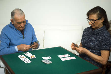 Elderly couple playing a game of cards photo
