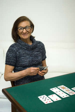 Senior woman playing cards photo
