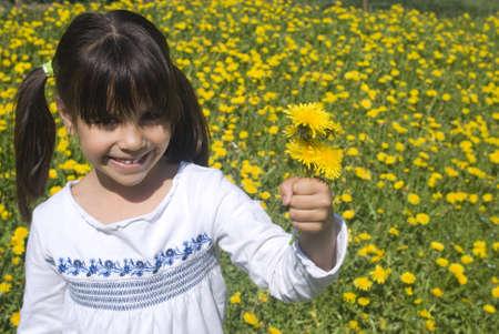 Feliz niño sonriente que da el regalo de las flores