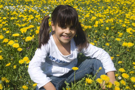 Young girl sitting in field of dandelions photo