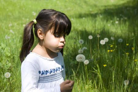 Girl blowing a dandelion photo