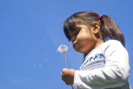 blowing dandelion: Ragazza tarassaco che soffia contro il cielo blu