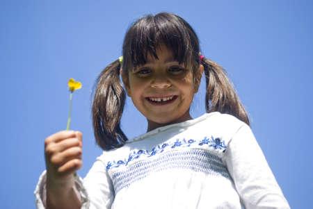 Girl holding flower. Portrait against blue sky photo