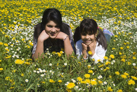 Happy sisters lying in spring meadow photo