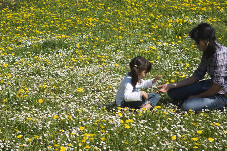 Two sisters playing in the meadow of spring Stock Photo - 10253459