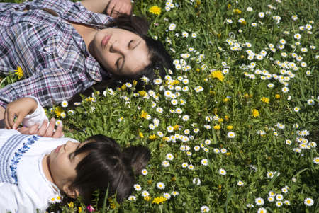 Sleeping girls relaxing on grass with eyes closed photo