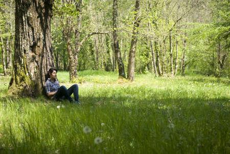 Adolescente relajante bajo un árbol