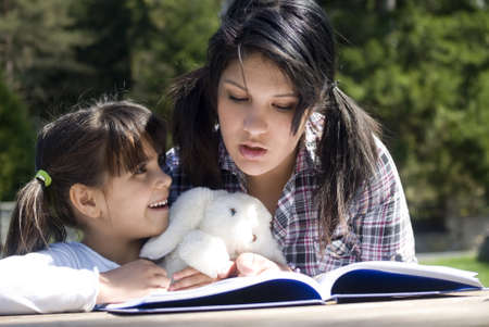 Teenage girl reads a story to little sister Stock Photo - 10253439