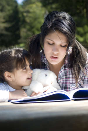 Teenage girl reads a story to little sister photo