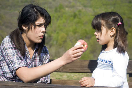 Teenage girl offering an apple to little sister photo