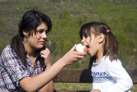 mixed age: Teenage girl offering an apple to little sister